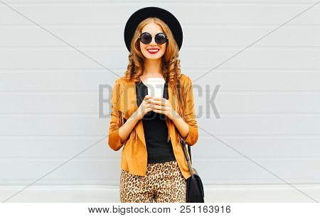 Elegant Woman With Coffee Cup Wearing Retro Elegant Hat, Sunglasses, Brown Jacket And Black Handbag