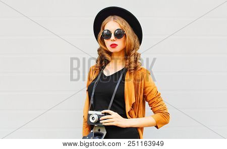 Cool Girl Model With Retro Film Camera Wearing Elegant Hat, Brown Jacket Posing Outdoors Over City G
