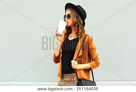 Young Woman Drinks Coffee Of Cup Wearing A Retro Elegant Hat, Sunglasses, Brown Jacket And Black Han