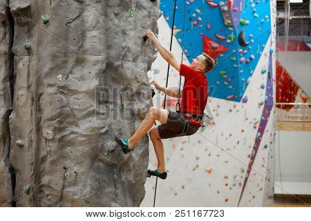 Photo from side of sports man exercising on climbing wall