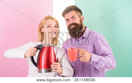 Man With Mug And Woman With Electric Kettle Ready To Drink Morning Coffee. First Thing They Do Every