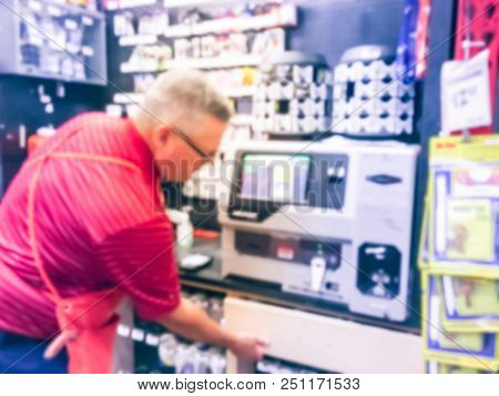 Vintage tone abstract blurred rear view employee operates key duplication machine at hardware store in USA poster