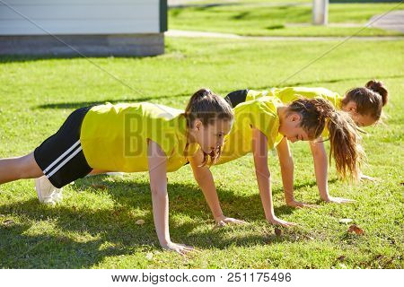 Friend girls teens push up push-ups workout ABS in a park turf grass