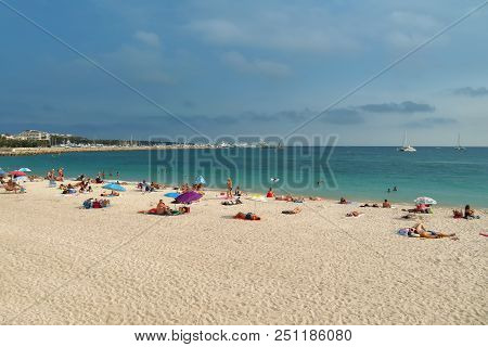 Cannes, France - July 3, 2018: Vacationers Enjoy The Beautiful Weather On The Public Beach.