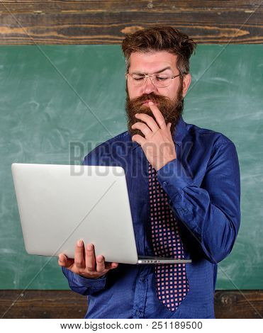 Distance Education Concept. Surfing Internet. Hipster Teacher Wear Eyeglasses And Necktie Holds Lapt