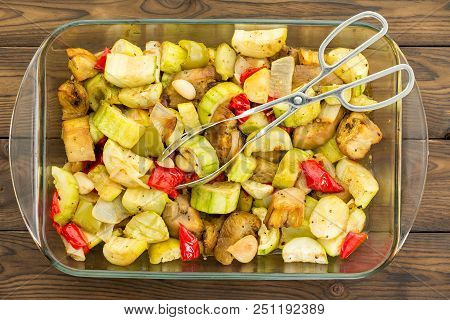 Overhead View Of Rectangular Glass Casserole Dish Filled With Savory Roasted Vegetables Set On A Woo