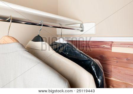 Three Suits Hanging In A Cedar Closet