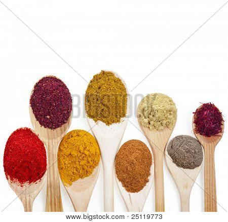 powder spices on spoons isolated  on a white background