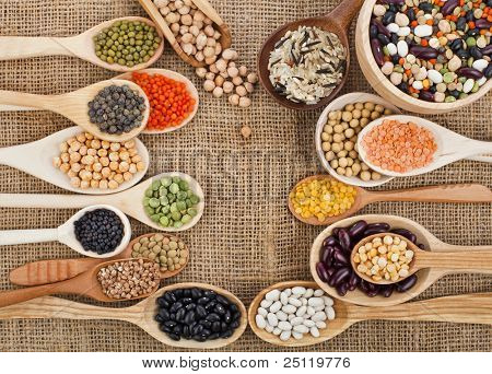 various food ingredients : beans, legumes, peas, lentils in wooden spoon on the sackcloth background