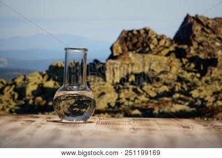 Clean water in a glass laboratory flask on wooden table on mountain background. Ecological concept, the test of purity and quality of water.