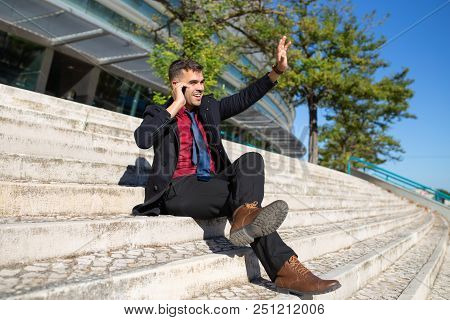 Positive Excited Businessman Waving Hand While Talking On Phone. Cheerful Handsome Young Hispanic Ma