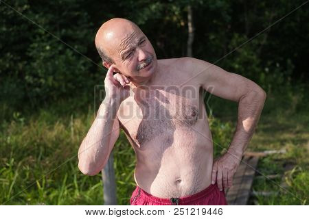 Mature European Man With Mustache Trying To Pull Water Out Of Ear After Swimming In Lake Or River. E