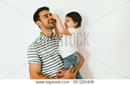 Happy Cute Little Girl And Her Handsome Father Are Hugging And Playing Together Against White Backgr