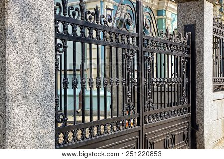 Part Of The Black Gate Of Steel Bars And Concrete Pillars