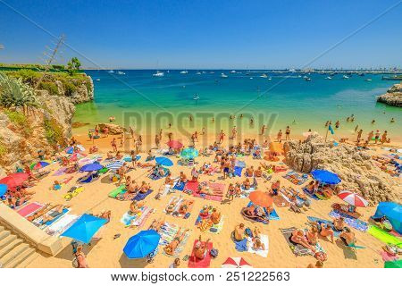 Cascais, Portugal - August 6, 2017: People Sunbathing On Praia Da Rainha, A Small Beach Sheltered By