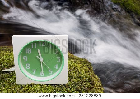 Table Clock On A Green Moss In Front Of Brook