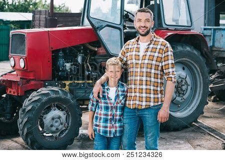 Happy Father And Son In Checkered Shirts Smiling At Camera While Standing Together Neat Tractor At F