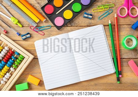 Back To School Concept. School Supplies And Blank Notebook On Wooden Background, Space For Text, Top