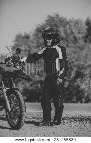 Man Posing Close To His Touring Motorbike In Black And White.