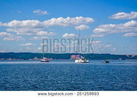 Two Sailing Boats And One Motor Boat On The River.