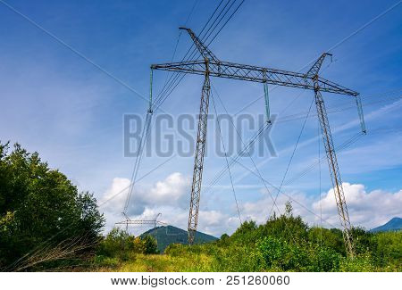 Power Line Tower On A Hillside. Giant Metal Construction In Beautiful Landscape. Power And Energy Co