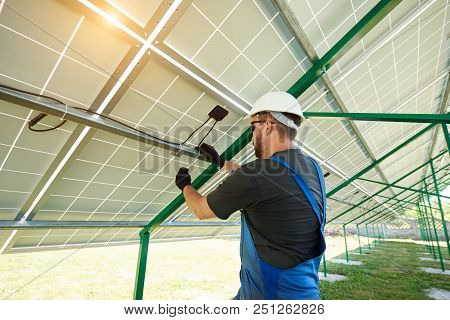 Worker Installing Solar Panels During Sunny Day. Perfect Solution For Saving Energy Of Sun, Environm