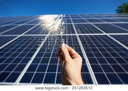 Frontview of worker's hand holding tiny detail for solar battery installing in front of solar pannel on background. Sunblinds on smooth surface. Innovative high-tech exterior. Environment friendly. poster