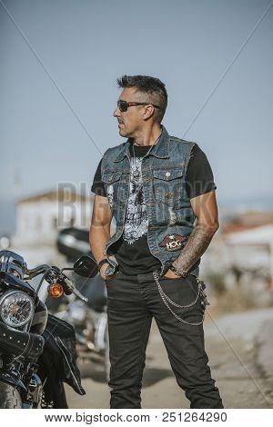 Malaga, Spain - July 15, 2018: Arms Crossed Man Waiting Close To His Harley Davidson Motorcycle Duri