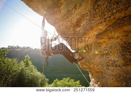 Image Of Man Climber In Helmet Clambering Up Cliff. Sunflare Effect.