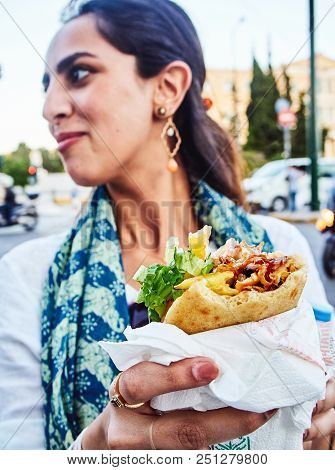 Greek Woman Eating A Gyros In A Street Of Athens.