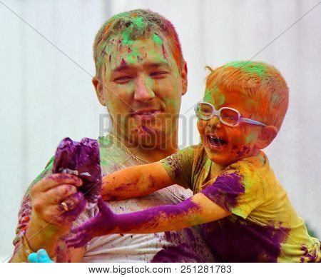 Moscow, Russia - July 14, 2018: Throwing Color At The Holi Color Festival. Happy Daddy And Son Durin
