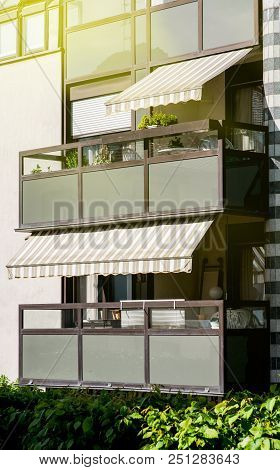 Apartment Building With Balcony With Awning Opened  - Covered By Sun-shield On A Warm Summer Day - S