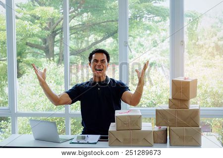 Start Up. Young Man Happy After New Order From Customer With Laptop Computer, Mobile Phone, Delivery