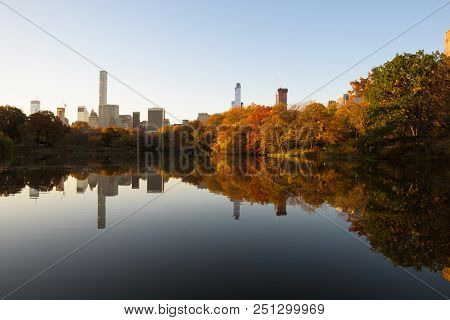 Skyline Of Manhattan Reflected In A Pond In Central Park At Sunrise, New York, United States Of Amer