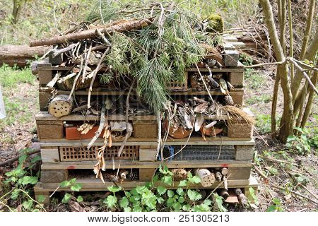 Bug Hotel For Insects And Other Animals Made From Pallets With Logs, Clay Pots, Bricks, Grass, Twigs