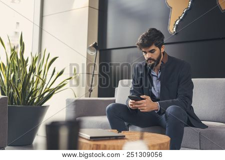 Businessman Sitting In A Modern Office, Typing A Text Message On A Smart Phone; International Compan