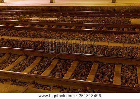 Railway Station Tracks At Night, Sleepers And Railroad Tracks.