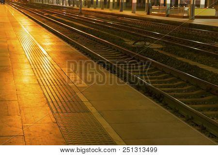 Railway Station Platform And Tracks At Night