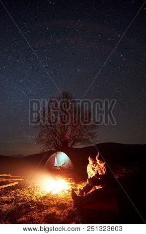 Camping Night In Mountains. Couple Tourists Boy And Girl Having A Rest Near Burning Bonfire Under St