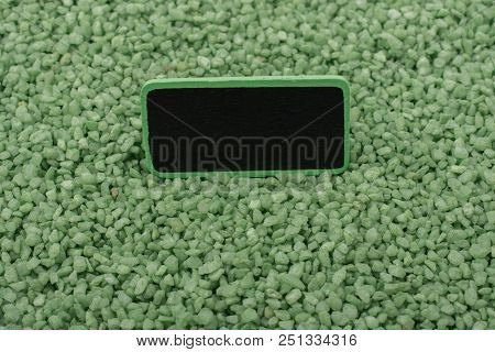 Noticeboard With Frame Placed On Green Color Sand