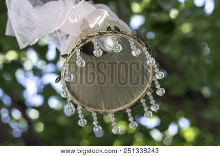Close-up Back Shot Of Handmade Oblation Figure Hanged On Tree With Transparent Stones By Green Backg