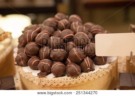Asorted chocolate truffles and pralines. Chocolate and coconut candies on the counter in the confectionery store. poster