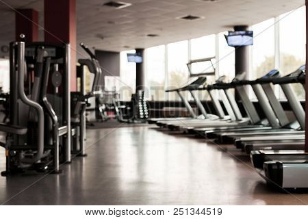 Gym Interior With Equipment. Light Modern Room With Row Of Treadmills And Fitness Stations. Concept
