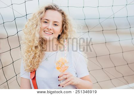 Optimistic Young Female Model With Curly Light Hair, Dressed In Casual White T Shirt, Drinks Fresh C