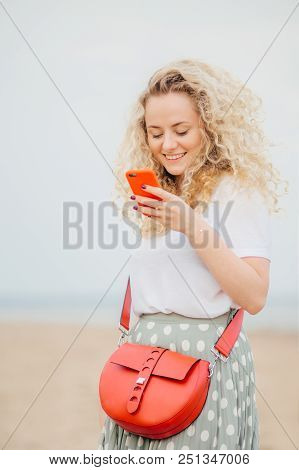 Positive Young Woman Uses Modern Smart Phone, Has Cheerful Expression, Makes Shopping Online, Carrie