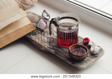 a cozy place to read on the windowsill - Asian tea, a warm scarf, a book, an atmosphere of coziness, inspiration, relaxation at home poster