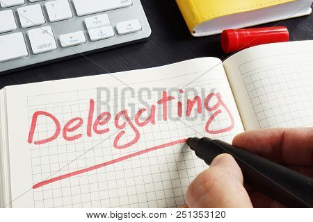 Man is writing delegating in the notepad. Delegate concept. poster