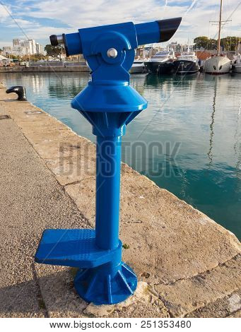 Blue Tourist Monocular For Sightseeing On The Background Of Yachts Standing In The Marina Of The Sea