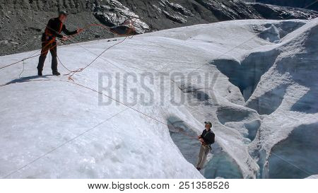 One Male Mountain Guide Installing A Pulley System For Crevasse Rescue On A Glacier