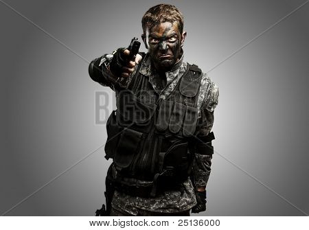 portrait of furious soldier with urban camouflage pointing with gun over grey background